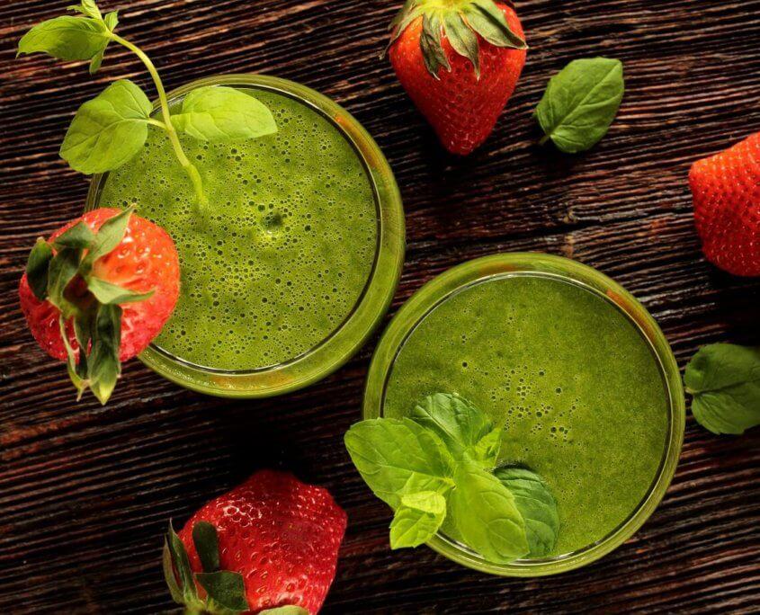 Sundhed og livsstil i form af grøn smoothie og jordbær som symboler på sundhed